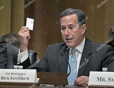 Stock Photo of Former Senator Rick Santorum shows off his health care insurance card as he testifies
