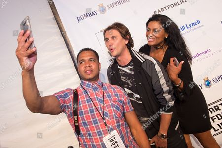 Johnny Nunez, left, Jonathan Cheban, middle, and Nina Cooper take a selfie at the 2016 Art For Life Benefit, presented by Russell Simmons' RUSH Philanthropic Arts Foundation, at Fairview Farms,, in Water Mill, New York