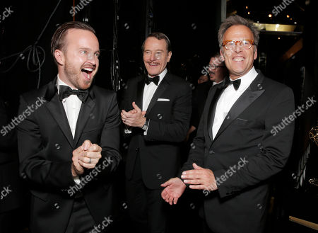 Aaron Paul, and from left, Bryan Cranston and executive producer Mark Johnson are seen backstage at the 66th Primetime Emmy Awards at the Nokia Theatre L.A. Live, in Los Angeles