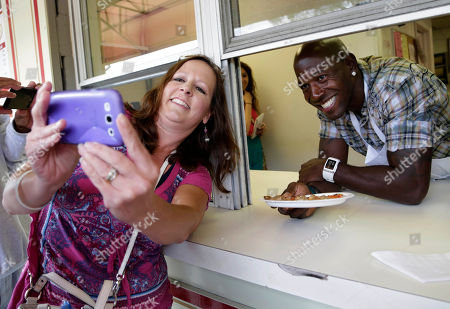 Green Bay Packer all-time leading receiver, Super Bowl Champion and Dancing with the Stars Champion Donald Driver serves up Zaffiros pizza to customers during Summerfest on behalf of U.S. Cellular in Milwaukee, Wis
