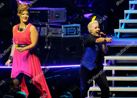 """Stock Image of Tessanne Chin, left, winner of season five of the reality television singing competition """"The Voice,"""" and season six contestant Kristen Merlin perform together during """"The Voice"""" 2014 Summer Tour stop at Nokia Theatre on in Los Angeles"""