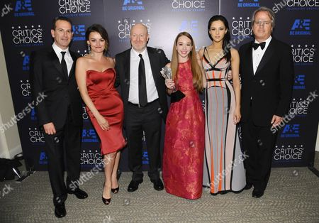 Darryl Frank, from left, Alison Wright, Joseph Weisberg, Holly Taylor, Annet Mahendru, and Graham Yost pose in the press room with the award for best drama series for The Americans at the Critics' Choice Television Awards at the Beverly Hilton hotel, in Beverly Hills, Calif