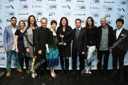 """Dirk Wilutzky, from fourth left, Mathilde Bonnefoy, Laura Poitras, Glenn Greenwald and the cast and crew of """"Citizenfour"""" pose in the press room with the award for best documentary at the 30th Film Independent Spirit Awards, in Santa Monica, Calif"""
