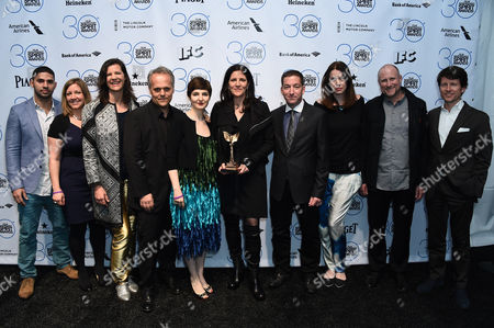 """Dirk Wilutzky, from fifth from left, Mathilde Bonnefoy, Laura Poitras, Glenn Greenwald and the cast and crew of """"Citizenfour"""" pose in the press room with the award for best documentary at the 30th Film Independent Spirit Awards, in Santa Monica, Calif"""