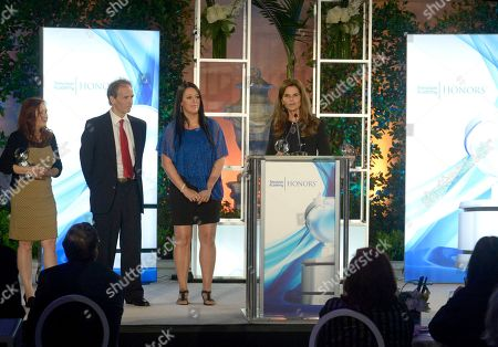 """Maria Shriver accepts the Television Academy Honors award for """"Paycheck to Paycheck"""" at the 8th annual Television Academy Honors at the Montage hotel, in Beverly Hills, Calif. From left, Shari Cookson, Nick Doob, and Katrina Gilbert look on"""