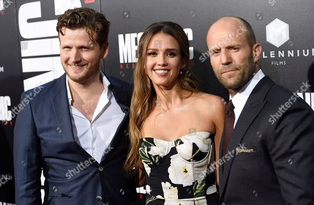 """Dennis Gansel, left, director of """"Mechanic: Resurrection,"""" poses with cast members Jessica Alba, center, and Jason Statham at the premiere of the film at the ArcLight Hollywood, in Los Angeles"""
