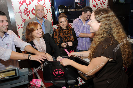 Stock Photo of Left to right) Christopher Manzo, Caroline Manzo, Albert Manzo, Lauren Manzo, and Albie Manzo work in the Hard Rock Cafe Rock Shop in support of the 13th Annual Pinktober Breast Cancer Awareness Campaign, on at Hard Rock Cafe, New York