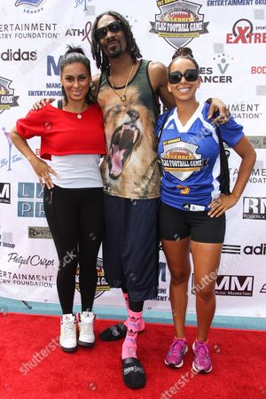 From left, TV personality Laura Govan, recording artist Snoop Dogg and TV personality Gloria Govan-Barnes attend the 1st Annual Athletes vs. Cancer Celebrity Flag Football game at the Palisades High School on in Pacific Palisades, Calif
