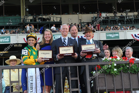 Jennifer Judkins, second left, and Charles Villoz, second right, both of Longines, award jockey Mike Smith, trainer Todd Pletcher and owner Cot Campbell, left to right, with their Longines Saint Imier timepieces after their horse Palace Malice won the 145th Belmont Stakes, in Elmont, NY. Longines, the Swiss watchmaker known for its elegant timepieces, is the Official Watch and Timekeeper of the 145th running of the Belmont Stakes
