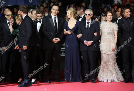 From left, Bruce Wagner, Evan Bird, John Cusack, Mia Wasikowska, David Croneberg, Julianne Moore and Robert Pattinson pose for photographers as they arrive on the red carpet for the screening of Maps to the Stars at the 67th international film festival, Cannes, southern France