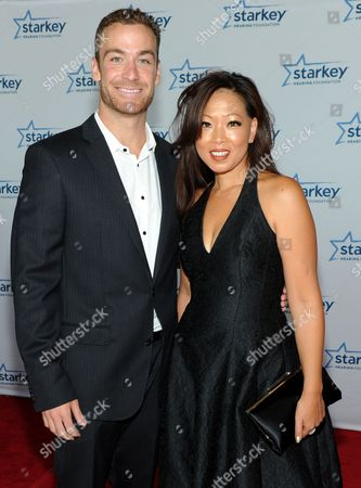 """Olympian Ed Moses and poker player Michelle Lau are seen on the red carpet at the Starkey Hearing Foundation's """"So the World May Hear"""" Awards Gala on in St. Paul, Minn"""