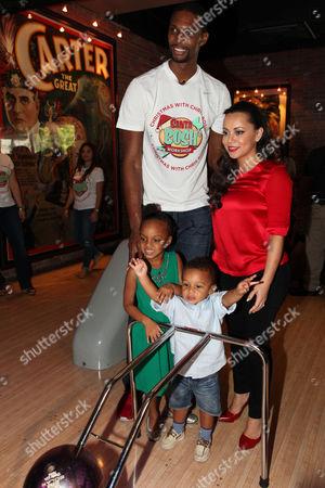 The Miami Heat's Chris Bosh and wife Adrienne Williams Bosh pose with their children during Team Tomorrow Inc. Celebrates Christmas at Santa Bosh Workshop on at Lucky Strike Lanes in Miami Beach, FL