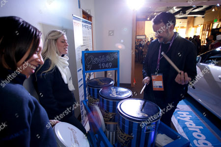 "Garrett Popcorn representatives Sarah Gruss, far left, and Crystal Allen look on as Stephen Kijak, the director of the Sundance film ""We are X"", uses the lids of popcorn tins as a drum set at the Toyota Mirai Music Lodge as part of the Sundance Film Festival, in Park City, Utah"
