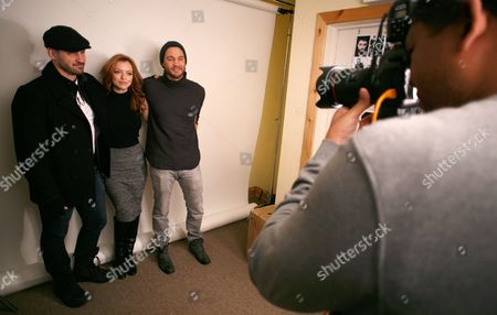 Outlaws and Angels director JT Mollner and actors Francesca Eastwood and Chad Michael Murray, from left, pose while Associated Press photographer Matt Sayles, right, captures images at the Toyota Mirai Music Lodge as part of the Sundance Film Festival, in Park City, Utah