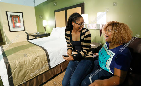 Food Network host Sunny Anderson, right, speaks with a fan in the Extended Stay America traveling hotel room at the New York City Wine & Food Festival