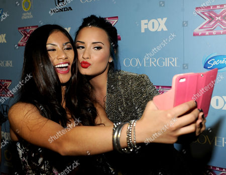 """From left, contestant Ellona Santiago and judge Demi Lovato arrive at FOX's """"The X Factor"""" Season 3 Finalists Party,, at the SLS Hotel in Beverly Hills, Calif"""