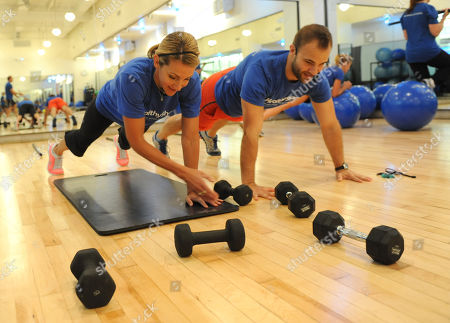 Olympian and mom Summer Sanders, left, helps launch the GE HealthyShare App for Facebook by demonstrating her workout challenge to an exercise class in New York, . Visit www.Facebook.com/Healthy to join and encourage your friends to take a step towards better health
