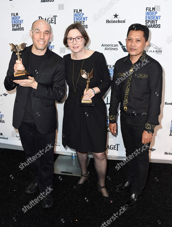 Joshua Oppenheimer, left, and Signe Byrge Sorensen, winners of the the award for best documentary for The Look of Silence pose with Adi Rukun in the press room at the Film Independent Spirit Awards, in Santa Monica, Calif