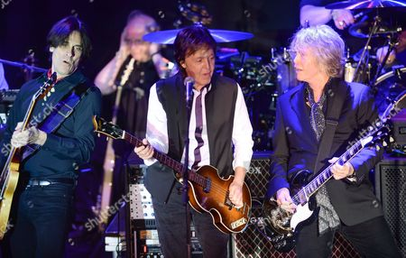 Paul McCartney, center, and his band, including Rusty Anderson, left, and Brian Ray, perform a secret Valentine's Day concert at Irving Plaza in New York. McCartney played a private concert with a crowd that included Wall Street executives and boldface names that included Sting and Oprah. The concert on Tuesday night, May 12, 2015, was part of the Robin Hood Foundation's annual benefit. Founded in 1988, the organization has raised more than $2 billion to combat poverty in New York's five boroughs