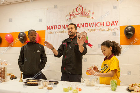 Chef Fabio Viviani, center, demonstrates making sandwiches with his assistants Johquary and Jurni on either side of him, during the Brownberry Bread National Sandwich Day Event at The Boys & Girls Jordan Club on in Chicago
