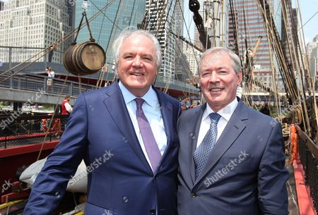 """Christophe Navarre, President and CEO of Moet Hennessy, left, and Jim Clerkin president and CEO of Moet Hennessy US pose for a photo with a special barrel of Hennessy seen hanging in the background at the """"Hennessy 250 Celebrates the Hermione's arrival in New York Harbor"""" at Pier 15, in New York"""