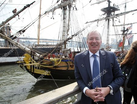 """Jim Clerkin President and CEO of Moet Hennessy US poses for a photo while the Hermioneis seen behind him coming into port at the """"Hennessy 250 Celebrates the Hermione's arrival in New York Harbor"""" at Pier 15, in New York"""