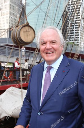 """Christophe Navarre President and CEO of Moet Hennessy poses for a photo with a special barrel of Hennessy is seen hanging in the back ground at the """"Hennessy 250 Celebrates the Hermione's arrival in New York Harbor"""" at Pier 15, in New York"""