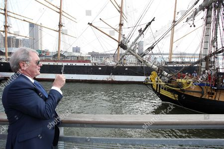 """Stock Picture of Jim Clerkin President and CEO of Moet Hennessy US is seen taking a photo of the Hermione while it is coming into port at the """"Hennessy 250 Celebrates the Hermione's arrival in New York Harbor"""" at Pier 15, in New York"""