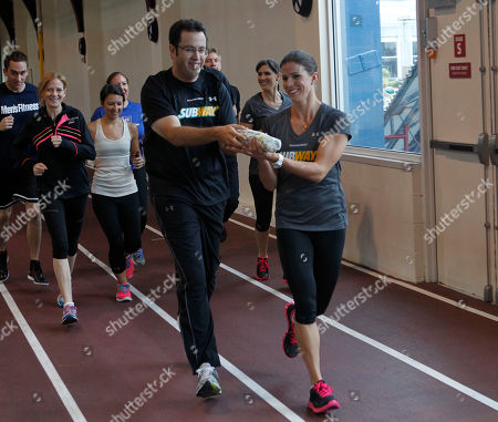 "Former Team SUBWAY marathoner Jared Fogle ""The SUBWAY Guy,"" passes the Footlong baton to Whitney Phelps, who announced she will run the ING New York City Marathon with Team SUBWAY at the Chelsea Piers Sport Center, in New York"