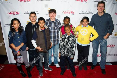 """Stock Photo of Diary of A Wimpy Kid author Jeff Kinney, right, and actor Robert Capron, center, meet with kids from the Carmelo Anthony Foundation on the red carpet to celebrate the """"Diary of a Wimpy Kid: Dog Days"""" Blu-ray debut on December 18th, at an exclusive screening event held on in New York. Hosted by Twentieth Century Fox Home Entertainment and the Carmelo Anthony Foundation, the family fun event took place at the AMC Empire 25 Theater"""