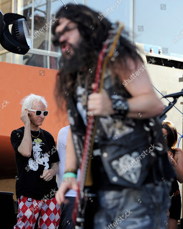 Robbie Krieger, left, guitarist for The Doors, puts in ear plugs as he watches Black Label Society perform at the Sunset Strip Music Festival, in West Hollywood, Calif