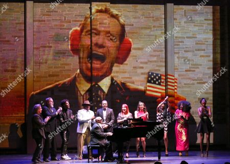 Ellis Hall performs at Backstage at the Geffen, in Los Angeles. Bryan Cranston is seen onscreen