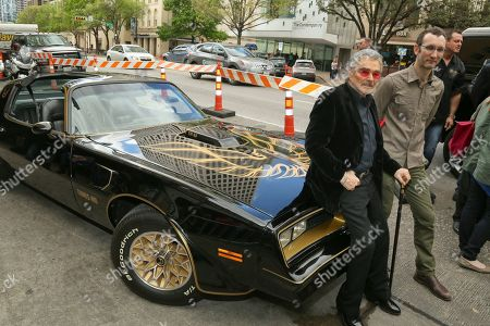 """Burt Reynolds, left, and director Jesse Moss pose next to a 1977 Pontiac Trans-Am at the world premiere of """"The Bandit"""" at the Paramount Theatre during the South by Southwest Film Festival, in Austin, Texas"""
