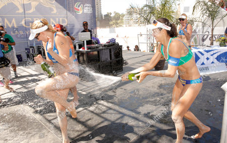 Talita Antunes sprays Jennifer Kessy with a bottle of Champagne at Celebrity Cruises' Taste of Modern Luxury Culinary & Spa Tour at World Series of Beach Volleyball Finals on in Long Beach, Calif