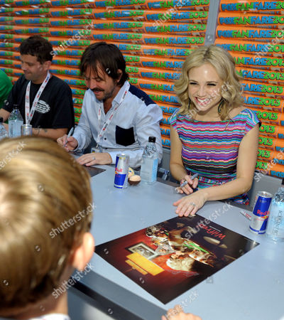 """From far left, producer Reed Agnew and cast members Jason Gann, and Fiona Gubelmann sign autographs at the FX """"Wilfred"""" booth signing on Day 2 of Comic-Con International on in San Diego, Calif"""