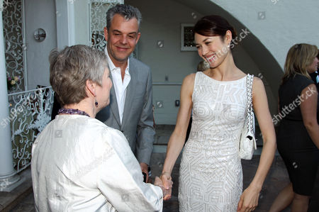 """Stock Image of Danny Huston, center, and Olga Kurylenko, right, greet Consul General Dame Barbara Hay at STARZ' """"The White Queen"""" cocktail event at the British Consulate on in Los Angeles. """"The White Queen"""" premieres Saturday, Aug. 10 on STARZ"""