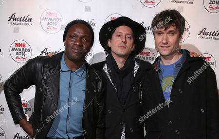From left, Gary Powell, Carl Barat and John Hassall from the band The Libertines poses for photographers upon arrival at the NME 2016 music awards in London