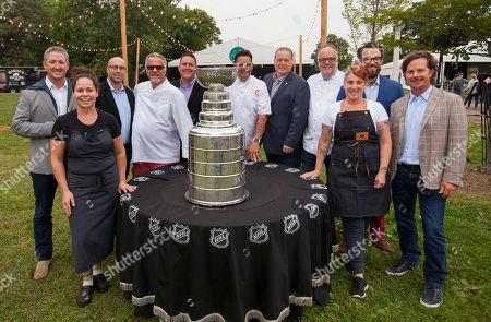 Tim Love, Stephanie Izard, Jim Clark, Jimmy Bannos Sr, Paul DeShaw, Graham Elliot, Larry O'Brien, Tony Mantuano, Mindy Segal, Danny Wirtz and Charlie Jones pose with the Stanley Cup at the Feast Under the Stars event during the Chicago Food + Wine Festival, in Chicago