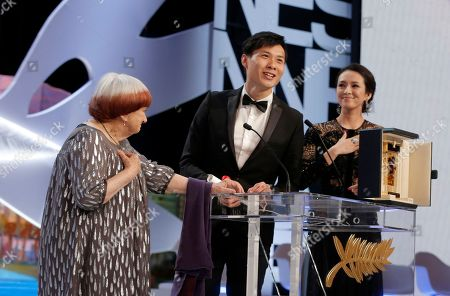 Director and jury member Agnes Varda, left, and jury member and actress Zhang Ziyi, right, present Anthony Chen, center, the Camera d'Or award for his film Ilo Ilo during an awards ceremony at the 66th international film festival, in Cannes, southern France