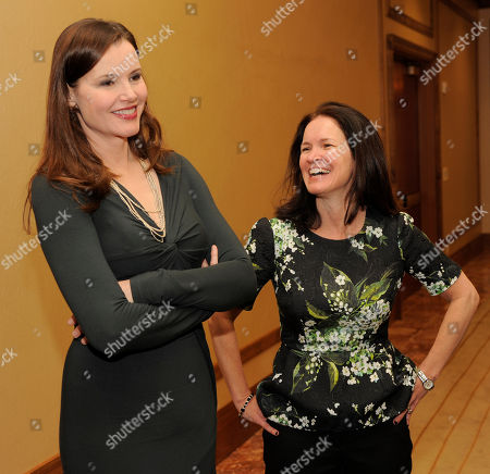 """Actress Geena Davis, left, and Amy Miles, CEO of Regal Entertainment Group, mingle before the """"Driving Financial Success: Women + Movies = Bigger Box Office"""" luncheon at CinemaCon 2013 at Caesars Palace on in Las Vegas"""