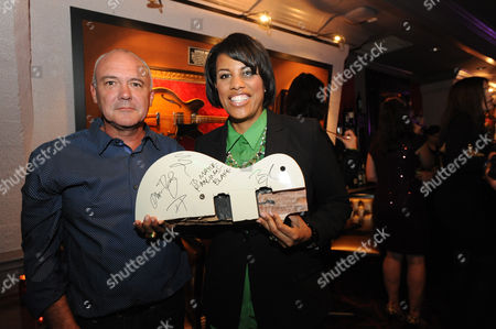 Hamish Dodds, President and CEO of Hard Rock International gives Mayor Stephanie Rawlings-Blake a signed Imagine Dragons guitar at the Grand Reopening party for Hard Rock Cafe Baltimore, on in Baltimore