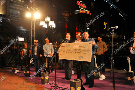 Left to right, Fred Thimm, Vice President and COO Corporate cafes of Hard Rock International, Casey Baynes, founder and executive director of the Casey Cares Foundation, and Hamish Dodds, President and CEO of Hard Rock International present a $10,000 donation to The Casey Cares Foundation at the Grand Reopening of Hard Rock Cafe Baltimore on