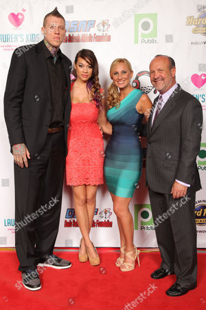 Miami HEAT Chris Andersen with guest Tina Wiseman pose with Lauren's Kids founder, Lauren Book and father Ron Book attend the Seventh Annual Reid & Fiorentino Call of the Game Dinner Presented by Publix at the Seminole Hard Rock Hotel & Casino on Saturday, March 9th, 2013 in Hollywood, Fl. Lauren Kids is a Florida-based organization aimed at preventing child sexual abuse and healing survivors through education and awareness. The organization, headquartered in Aventura, Florida, was started by Lauren Book, M.S. Ed., a survivor of childhood sexual abuse who endured abuse at the hands of her nanny for six years