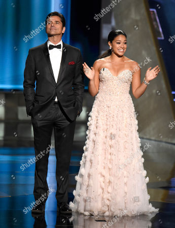 John Stamos, left, and Gina Rodriguez introduce presenters Joan Cusack and Bradley Whitford at the 67th Primetime Emmy Awards, at the Microsoft Theater in Los Angeles