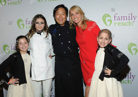 Singer Daya, second left, chef Ming Tsai, center, Family Reach National Advisory Board President, and Carla Tardif, center right, CEO, Family Reach, with twins Sabrina and Olivia Lorusso, attend Family Reach's Cooking Live! charity event, at The Ritz-Carlton New York, Battery Park. The event raises funds to help families facing the daily cost of cancer