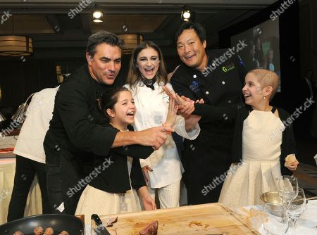 Chef Todd English, singer Daya, and chef Ming Tsai, left to right, with twins Sabrina and Olivia Lorusso, front, celebrate at Family Reach's Cooking Live! charity event, at The Ritz-Carlton New York, Battery Park. The event raises funds to help families facing the daily cost of cancer