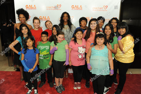 Shondrella Avery, center, and CoachArt kids arrive at the CoachArt Gala of Champions held at The Beverly Hilton, in Beverly Hills, Calif