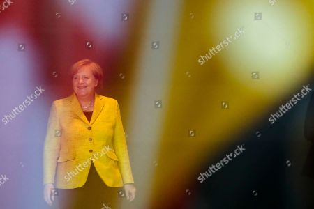 Through a window with a reflection of the German flag, German Chancellor Angela Merkel waits for the arrival of Georgian Prime Minister Giorgi Kvirikashvili for talks at the chancellery in Berlin