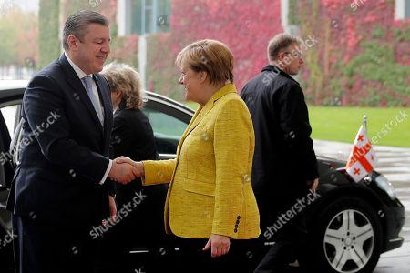 German Chancellor Angela Merkel, center, welcomes Georgian Prime Minister Giorgi Kvirikashvili, left, for talks at the chancellery in Berlin