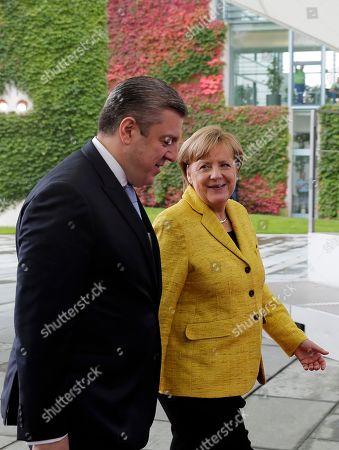 German Chancellor Angela Merkel, right, welcomes Georgian Prime Minister Giorgi Kvirikashvili, left, for talks at the chancellery in Berlin